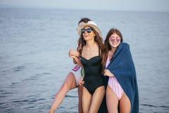 Donne sulla spiaggia con il plaid dopo avere uguagliato, vacanze estive, feste, viaggio fotografia stock libera da diritti