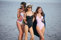 Donne sulla spiaggia con il plaid dopo avere uguagliato, vacanze estive, feste, viaggio immagini stock