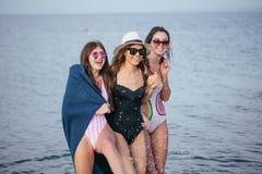 Donne sulla spiaggia con il plaid dopo avere uguagliato, vacanze estive, feste, viaggio immagine stock