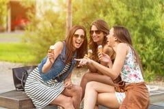 3 donne sveglie, saloni di gelato, mentre ridendo Fotografia Stock