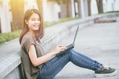 Donne teenager in università facendo uso dello stile di vita moderno del computer portatile e dello smartphone Fotografia Stock