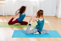 Donne in un asana fornito di gambe del piccione di re nel centro di yoga Fotografia Stock