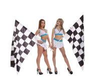 Donne in uniforme con le bandiere a quadretti della corsa Fotografia Stock