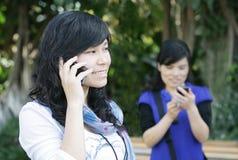 donne usando graziose dei telefoni delle cellule Fotografia Stock