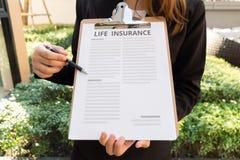 Donne in vestito che mostra politica di assicurazione sulla vita e che indica con la a Fotografia Stock