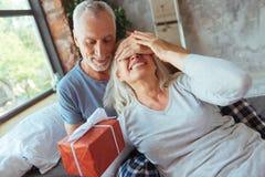 Donner âgé aimant d'homme actuel à sa gentille épouse Photo stock