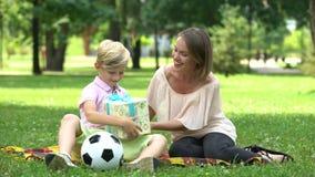 Donner affectueux de mère actuel au fils sur l'anniversaire, incorporation de rêve d'enfant banque de vidéos