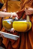 Donner aux objectifs des moines thaïlandais. Image stock