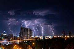 Donner, Beleuchtung und Sturm im dunklen nächtlichen Himmel über Stadt Stockfoto