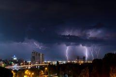 Donner, Beleuchtung und Sturm im dunklen nächtlichen Himmel über Stadt Stockfotografie