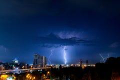 Donner, Beleuchtung und Sturm im dunklen nächtlichen Himmel über Stadt Stockfotos