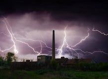 Donner, Blitze und Sturm über verlassener Fabrik im Sommer Stockbilder