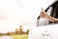 Donner de main pouces vers le haut de jet de signe que la fenêtre d'une voiture a garé près des routes Le symbole d'une main a au Photo stock