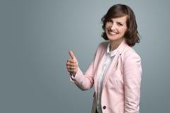 Donner de sourire de femme des pouces lèvent le signe Image libre de droits