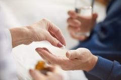 Donner des pilules à l'homme supérieur images stock