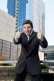 Donner heureux et enthousiaste de jeune homme d'affaires réussi manie maladroitement vers le haut du signe correct Photos stock