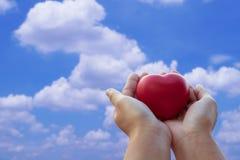 Donner l'amour et le concept de valentine, main tenant le coeur rouge sur le soleil Photo stock