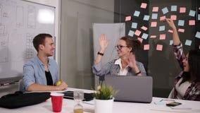 Donner réussi heureux d'équipe d'affaires des jeunes de hauts fives font des gestes pendant qu'elles rient et encouragent leur su banque de vidéos