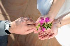 Donner un marié lilas de fleur à la jeune mariée pour offrir son amour Images libres de droits