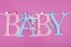 Donner un petit coup rose et bleu de crèche de bébé de lettres Photographie stock libre de droits
