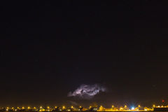 Donner-Wolke über dem Dorf und dem Blitz, die aus sie herauskommen Lizenzfreies Stockbild