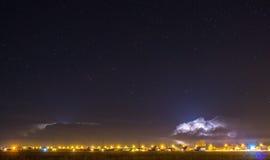 Donner-Wolke über dem Dorf und dem Blitz, die aus sie herauskommen Stockbild