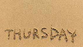 Donnerstag - Wort gezeichnet auf den hellen gelben Strandsand Auszug Stockbild