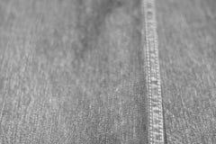 Donnez au fond une consistance rugueuse des jeans foyer mou, tache floue de dos, noire et blanche Photographie stock