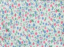Donnez au tissu une consistance rugueuse tricoté par blanc en petites fleurs roses et bleues Photo libre de droits