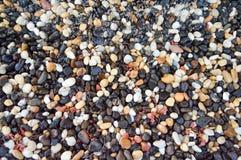 Donnez aux différentes pierres une consistance rugueuse peu communes humides avec de l'eau du rond naturel rouge blanc de brun ja photo stock