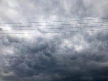Donnez aux fils une consistance rugueuse à haute tension tendus noirs pour l'électricité sur un fond des nuages de pluie orageux  photo stock