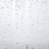 Donnez aux gouttes une consistance rugueuse de l'eau sur le verre transparent, fond abstrait Images stock