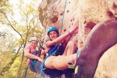 Donnez des leçons particulières à la fille de enseignement montant une roche avec des harnais Photographie stock libre de droits