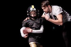 Donnez des leçons particulières à regarder le joueur de football américain de garçon courant avec la boule Image libre de droits