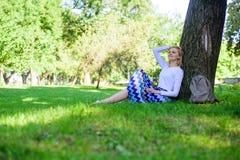 Donnez-vous la coupure et appréciez les loisirs Trouvez l'endroit paisible en parc La fille s'asseyent sur le maigre d'herbe sur  photos stock