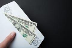 Dono in una busta su un fondo nero, spazio vuoto del dollaro per testo fotografia stock libera da diritti