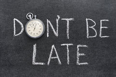Dont be late. Don't be late phrase handwritten on chalkboard with vintage precise stopwatch used instead of O Stock Photo