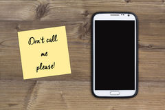Dont call me please message, smart phone and sticky note on wood Royalty Free Stock Photo