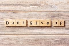 Dont give up word written on wood block. Dont give up text on table, concept stock image