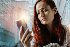 Sad young woman sitting and using the cellphone. Dont leave me. Sad young pretty woman sitting at home holding and using the cellphone Royalty Free Stock Image