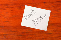 Dont Miss - Post it Note on Wood Background Royalty Free Stock Photos