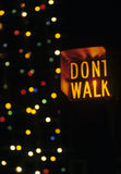 Dont walk. A dont walk sign sits in front of a lit up christmas tree Royalty Free Stock Photography