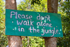 Dont walk alone in the jungle sign board on the tr. Dont walk alone in the jungle sign on Koh Rong island Cambodia Royalty Free Stock Photo