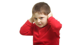 Dont want to hear. Boy in red sitting and closing his ears with palms Stock Photo