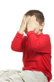 Dont want to see. Boy in red sitting and closing his eyes with palms Stock Photos