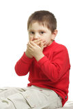 Dont want to talk. Boy in red sitting and closing his mouth with palms Royalty Free Stock Photography