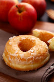 Donut. A sugar glazed donut on wood Stock Images