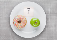 Donut and apple healthy food choices on the plate Royalty Free Stock Images