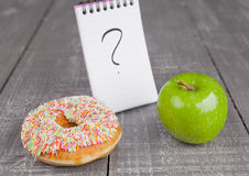 Donut and apple healthy food choices on wooden board Stock Photos