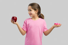 Donut or Apple. Little girl smiling and choosing between a apple and a donut Royalty Free Stock Photography